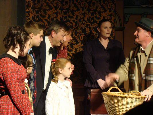 (l to r) Janie (Adell Detwiler) Pete (Joshua Thomason) Tommy (Timothy Edwards) George Bailey (Paul Ballard) Zuzu (Michaela Shunk) Mary Hatch (Christine Alfano) Bank Examiner Carter (Becky Kopp) and Uncle Billy (Tom Delaney)