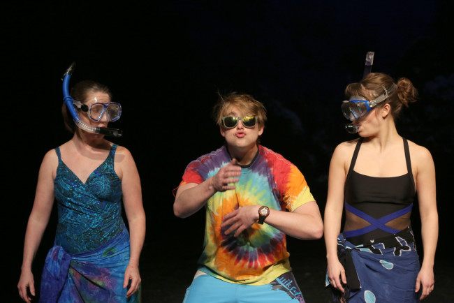 Susan (L- Marianne Angelella) and Sarah (R- Kathryn Zoerb) take snorkeling instructions from an Island Dude (C- Travis Hudson) on the beaches of Hawaii