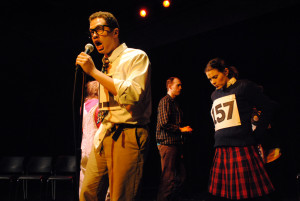 Jonathan Miot as William Barfee (at the microphone)