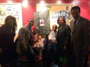 Evan Alston (to the right of the poster) and family celebrate Alston's success as a young playwright