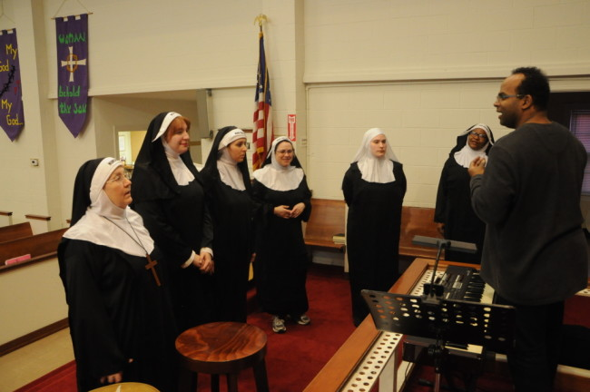 The Nuns rehearse for their talent show with Keyboardist Vince Evans (right)