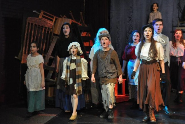 "Gavroche (Center-left: Dylan Morrison) and Eponine (Center-right: Ilyssa Rubin) sing ""One Day More"" with the ensemble of Les Miserables"