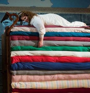 Princess Winnifred (Amy E. Haynes) attempting to sleep atop the 20 mattresses (Conceived by Set Designer Elizabeth Tane Kanner)