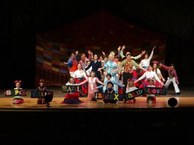 "The company of Mary Poppins at September Song in Mrs. Corry's talking shop, singing ""Supercalifragilisticexpialidocious"""