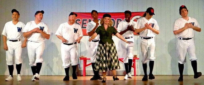 Ashley Gerhardt (center) as Reporter Gloria Thorpe and the Baseball Ensemble of Damn Yankees at The Heritage Players