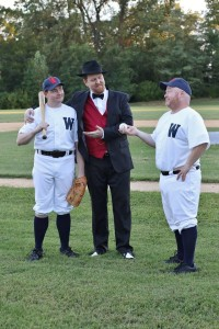 Joe Hardy (L- Jim Gerhardt), Mr. Applegate (C- Ryan Geiger), and Coach Van Buren (R- John Sheldon) discuss a contract
