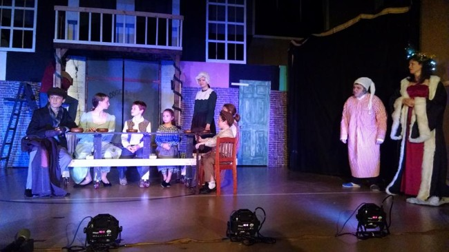 Bob Cratchit (far left- Cameron Walker) and family with Scrooge (right- Annie Gorenflo) and Christmas Present (far right- Katie Evans)