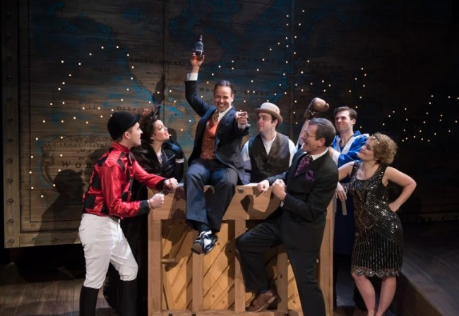 Noah Racey (center atop the piano) as Wilson Mizner and the ensemble of Road Show at Signature Theatre