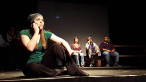 Zoe Bulitt (foreground) as Tectonic Theater Project Company Member Amanda Gronich calling the Minister's Wife (background center, Natalie McManus) in The Laramie Project