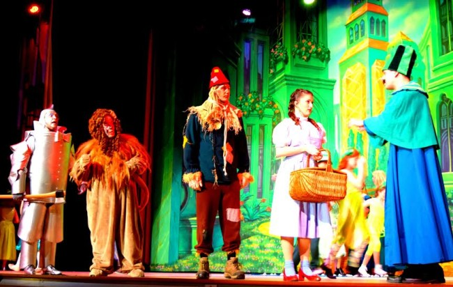 (L to R) Michael Quinn as Tinman, John Sheldon as Cowardly Lion, Jamie Austin Jacobs as Scarecrow, Lucy Bobbin as Dorothy, and John Machovec as The Gatekeeper in The Wizard of Oz