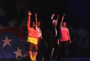 "Willy LaHood (center) as Bernie Sanders and (in no particular order) Kandace Foreman, Jamie Sinks, Kathleen Suydam, and Roxanne Waite as his go-go dancers for ""Feel the Bern"""