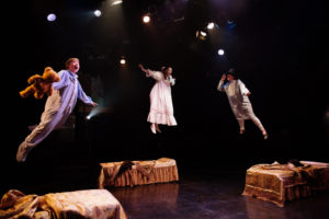 Gavin Willard (left) as Michael Darling, Katie Tyler (center) as Wendy Darling, and Brian Rusk (right) as John Darling flying through the nursery in Peter Pan