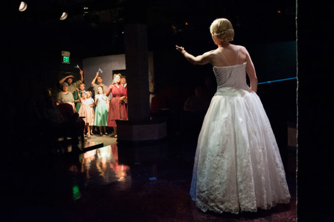Becca Vourvouas (right) as Eva Perón and the people of Argentina in Evita at Spotlighters Theatre