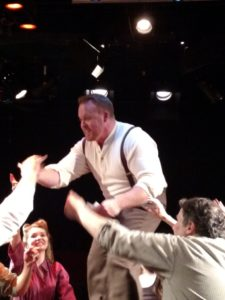 A tech-week rehearsal photo of Rob Wall (center) as Ché in Evita at Spotlighters Theatre