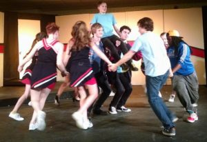 Pierce Elliott (center) as Evan on the shoulders of Jake Clark (left) as Ritchie and Jake Schwartz (right) as Bret and the ensemble of 13: The Musical