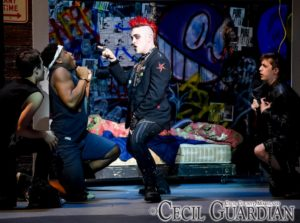 Shane Lowry (center) as St. Jimmy and the ensemble of American Idiot at Milburn Stone Theatre