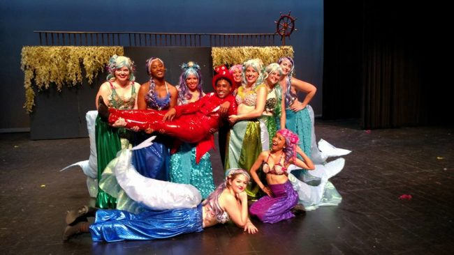 Brandon Shaw (center) as Sebastian and the Mersisters of Charm City Player's The Little Mermaid