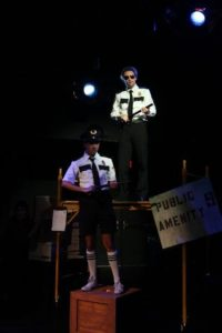 RJ Pavel (below) as Officer Barrell and Alan Naylor (above) as Officer Lockstock in Urinetown: The Musical