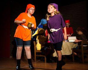 Doc (Maggie Walker) and Dopey (Ruby McKerrow), background: Sneezy (Veronica King), Bashful (Amenah Kitchens), Happy (Molly Ross), Grumpy (London Leyda)