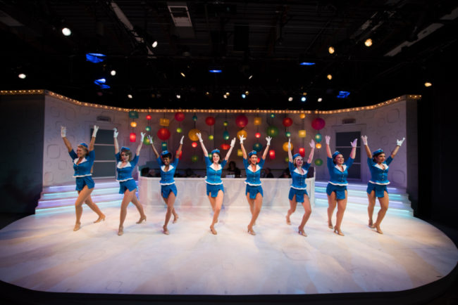 "(L-R) Corinne Holland, Mackenzie Newbury, Patricia ""Pep"" Targete, Carolyn Burke, Hannah Jennens, Alexis Kray, Melrose Pyne, and Ariana Kruszewski as Frank Abagnale Jr. Dancers in Catch Me If You Can at NextStop Theatre"