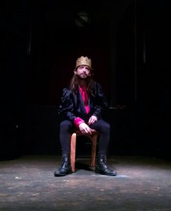 "Junius Brutus Booth (Scott Burke) alone on his throne as Richard III in ""His Majestic Lump of Foul Deformity"""