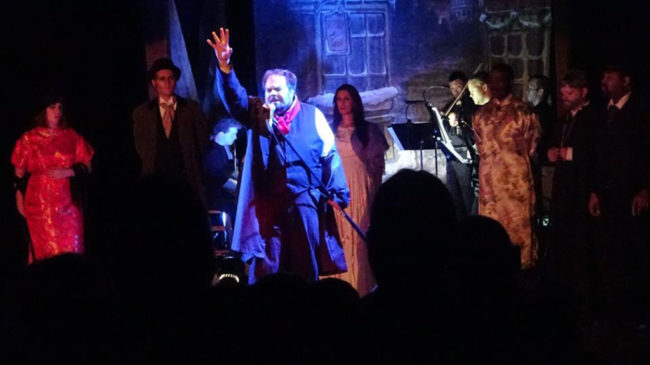 "Andrew Lloyd Baughman (center) as John Jasper singing ""Jasper's Confession"" in The Mystery of Edwin Drood"