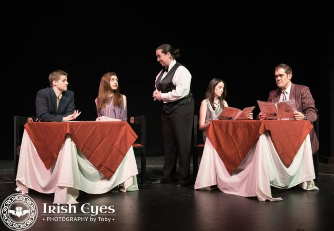 A young writer, Adam (Scott Duvall), and an android performer, Jacie (Caity Brown), are welcomed to a restaurant by a server (Bridgette Saverine). Another couple, (Emma Safford and Stephen T. Wheeler) peruse the menu.