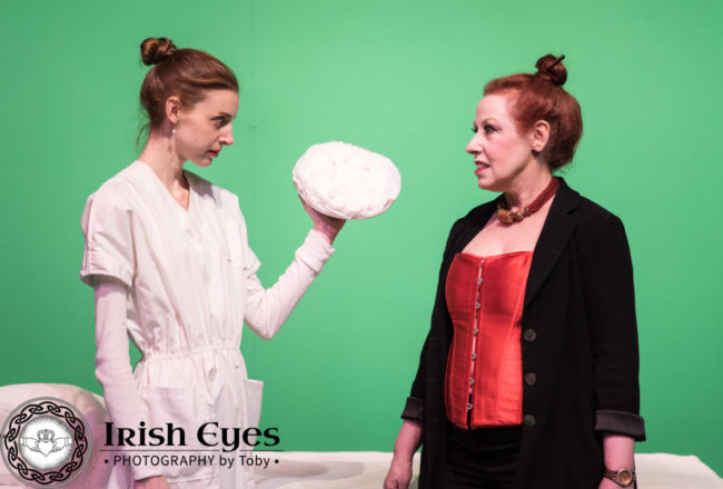 Jacie (Caity Brown), an android performer, prepares to throw a pie at Carla (Diane Sams), the Regional Director.