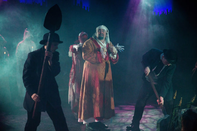 David Bosley-Reynolds (center) as Ebenezer Scrooge and the company of A Christmas Carol