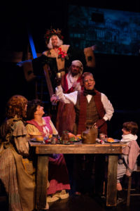 Darren McDonnell (top center) as Ghost of Christmas Present with David Bosley-Reynolds (center) as Ebenezer Scrooge and The Cratchit Family (below, L to R) Katie Tyler as Martha, Tina DeSimone as Mrs. Cratchit, David James as Bob, and Lucas Bromberg as Tiny Tim