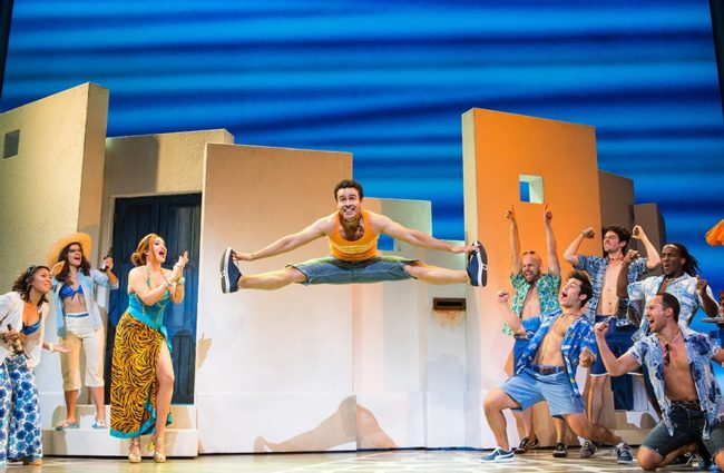 Cashelle Butler (center left) as Tanya with Austin Michael (jumping center) as Pepper and the company of Mamma Mia