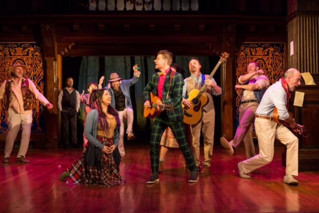 The cast of Folger Theatre's production of Shakespeare's As You Like It in exuberant song.