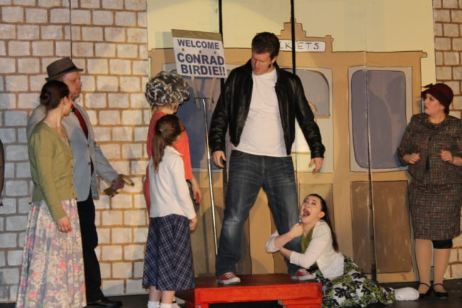 Matt Peterson (center) as Conrad Birdie with Olivia Winter as Ursula Merkel clinging to his leg with the Sweet Apple teens and parents
