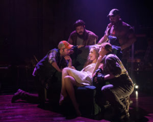 Morgan Keene (seated center) as Stina and the Hired Boys (Evan Casey, Jp Sisneros, Chris Sizemore, Stephen Gregory Smith) in Midwestern Gothic