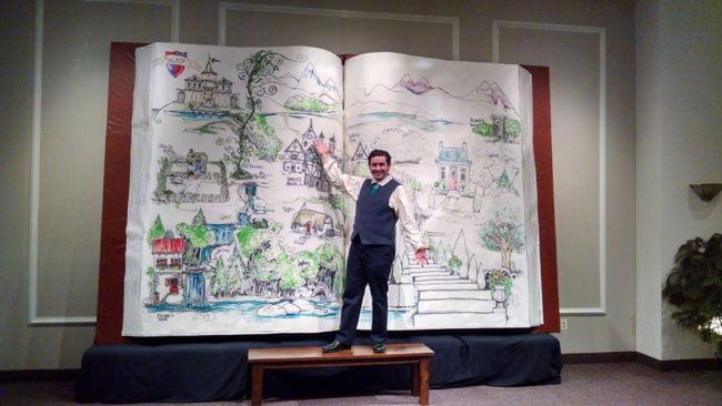 Alexander Foley (as the Mysterious Man) proudly showcases the storybook set piece created by Anne and Greg Foley for Storytellers: A Theater Arts Academy's production of Into the Woods