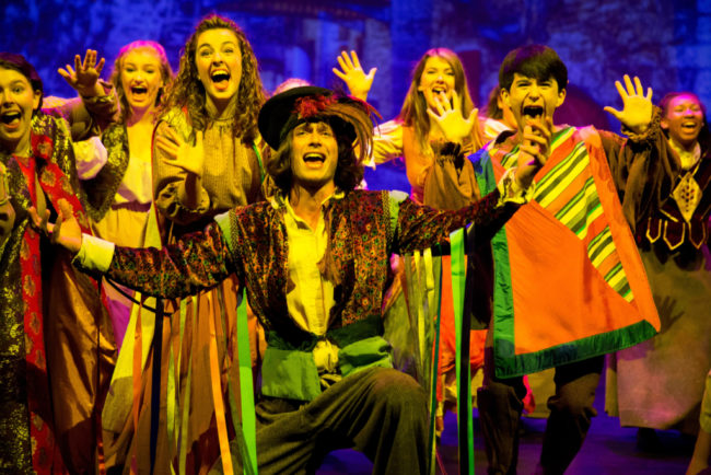 Joshua Huff-Edsall (center) as Clopin Trouillefou and the gypsies