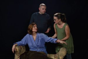 Rebecca Downs (seated) as Dr. Katherine Brandt, Paul Valleau (standing left) as Nurse Mike Clark and Victoria Scalfaro (standing right) as Clara