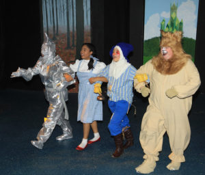 (L to R) Marie Nearing as The Tin Man, Loraine Hamlett as Dorothy, Sarah Dallas DeFord as Scarecrow, and Stephen P. Yednock as Cowardly Lion
