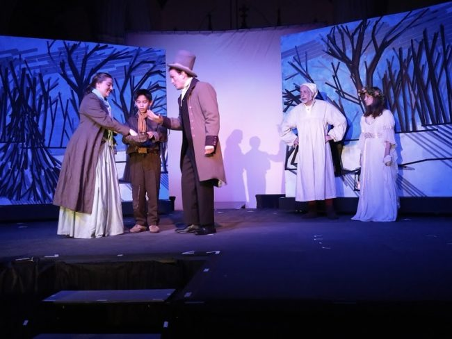 (L to R) Karissa Strawley Bryant as Bell, Alexander Walston-Valdas as caroling orphan boy, Ewan MacLean as Young Man Ebenezer, Richard Peck as Ebenezer Scrooge, and Petra McGregor as the Ghost of Christmas Past