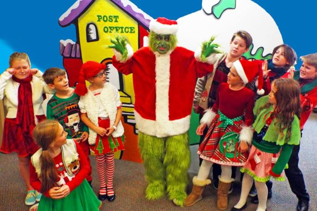 Jim Rose (center) as The Grinch, surrounded by the Whos of Whoville