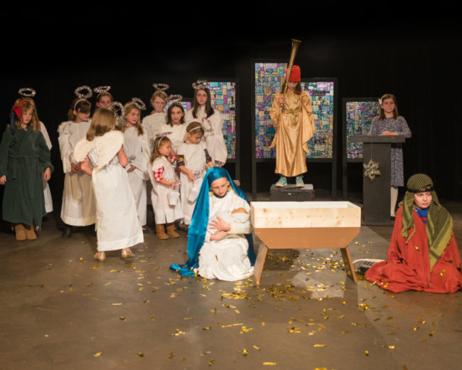 Lottie Doughty (kneeling left of the manger) as Imogene Herdman with Alice Levings (standing center above the manger) as Gladys Herdman, and Noah Davenport (kneeling right of the manger) as Ralph Herdman and the cast of The Best Christmas Pageant Ever at Silver Spring Stage