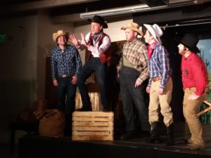 Joe Weinhofer (center) as Will Parker with the male ensemble in Oklahoma!