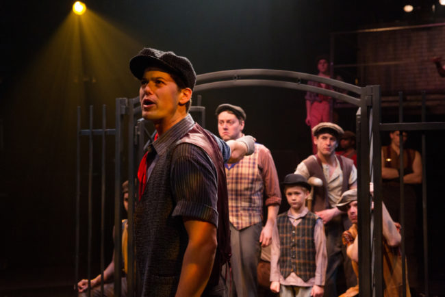 "Matt Hirsch (center) as Jack Kelly with the Newsies singing ""Seize The Day"" in Newsies at Toby's Dinner Theatre"