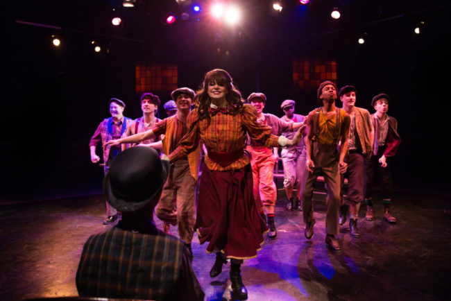 MaryKate Brouillet (center) as Katherine Plumber and The Newsies