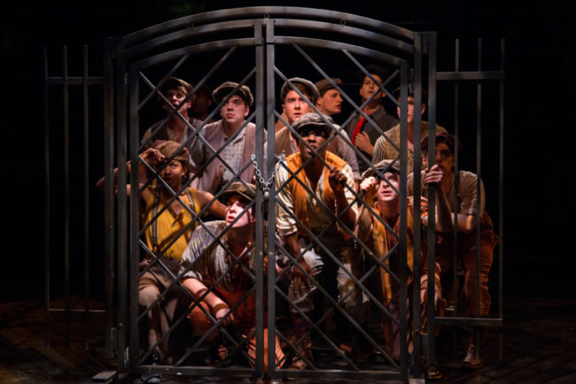 Newsies at the gates of The World in Newsies at Toby's Dinner Theatre