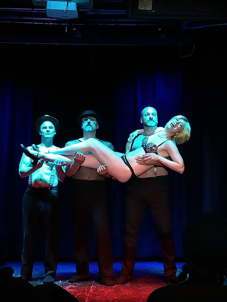 Kaylee Kalliope (center) as Roxie Hart with Scruffy Westside (left), Dirk Hamfist (center), and Ivan Hammer (right) in Chicago: A Burlesque Review