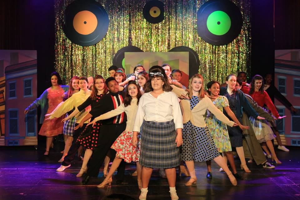 Valerie Ziegler (center) as Tracy Turnblad andthe ensemble of Hairspray at Children's Playhouse of Maryland