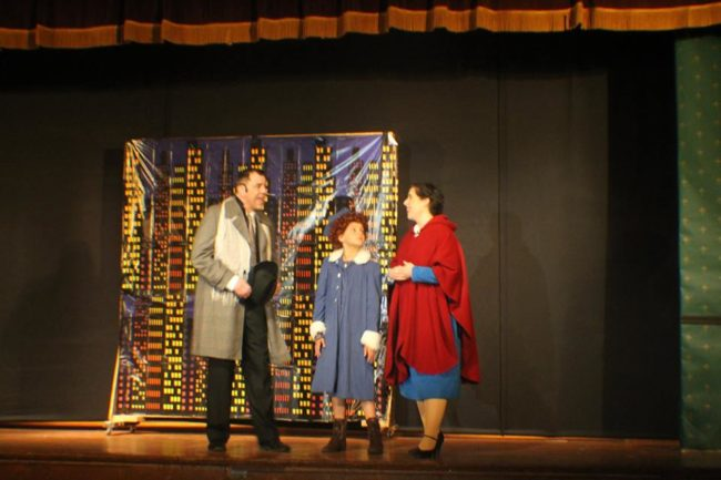 Doug Kotula (left) as Oliver Warbucks, Mia Novak (center) as Annie, and Lauren DeSha (right) as Grace Farrell