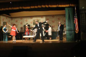 (L to R) Lauren DeSha as Grace Farrell, Mia Novak as Annie, Dough Kotula as Oliver Warbucks, and Forest Deal as Drake