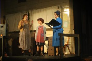 Heidi Toll (left) as Miss Hannigan, Mia Novak (center) as Annie and Lauren DeSha (right) as Grace Farrell